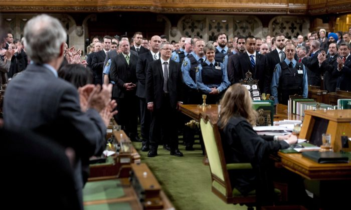 House of Commons security personnel receive a standing ovation on Dec. 11, 2014, from members of Parliament as they are honoured for their efforts during the October shooting on Parliament Hill. RCMP are will soon take control of security inside the Parliament Buildings. (The Canadian Press/Adrian Wyld)