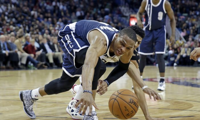 Oklahoma City Thunder guard Russell Westbrook (0) battles for a loose ball against New Orleans Pelicans forward Anthony Davis, behind, in the first half of an NBA basketball game in New Orleans, Wednesday, Feb. 4, 2015. The Thunder won 102-91. (AP Photo/Gerald Herbert)