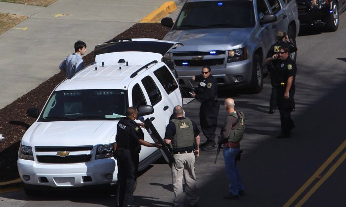 Law enforcement officials gather on the campus of the University of South Carolina in Columbia, S.C., after shots were fired at its new School of Public Health, Thursday, Feb. 5, 2015. There were no immediate reports on injury or suspects. (AP Photo/The State, Tim Dominick)