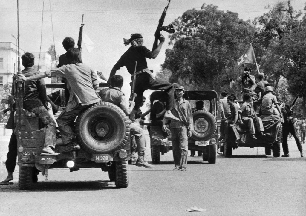 The Khmer Rouge guerilla soldiers wearing black uniforms, ride atop jeeps through a street of Phnom Penh, the day Cambodia fell under the control of the Communist Khmer Rouge forces, on April 17, 1975. (Sjoberg/AFP/Getty Images)
