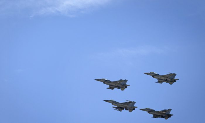 Jordanian Air Force fighter jets fly during the funeral of slain Jordanian pilot, Lt. Muath al-Kaseasbeh, at his home village of Ai, near Karak, Jordan, on Feb. 4, 2015. (AP Photo/Nasser Nasser)