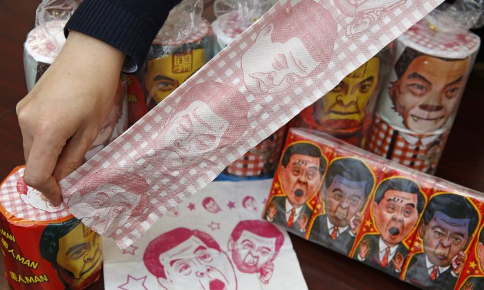 Hong Kong Democratic Party Vice Chairman Lo Kin-hei shows off rolls of toilet paper and packages of tissue paper printed with images of pro-Beijing Hong Kong Chief Executive Leung Chun-ying at his office in Hong Kong Saturday, Feb. 7, 2015. (AP Photo/Kin Cheung)