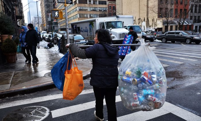 A woman balances a load of recyclable cans and bottles she collected from trash cans to sell in Manhattan on Jan. 30, 2015. New claims for U.S. unemployment insurance benefits plunged to the lowest level in nearly 15 years, the Labor Department reported. (Jewel Samad/AFP/Getty Images)