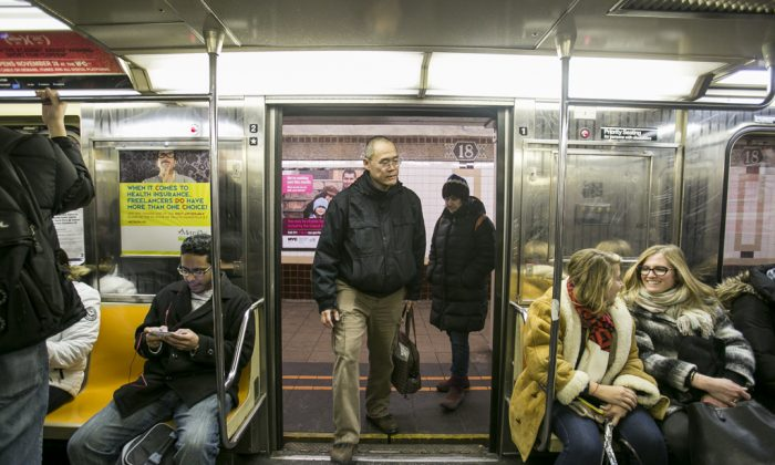 A man enters the 1 train at the 18th St. subway station in Manhattan, New York, on Feb. 1, 2015. Even though subway cars are teeming with microbial life, it's not something New Yorkers need to worry about, according to new research. (Samira Bouaou/Epoch Times)