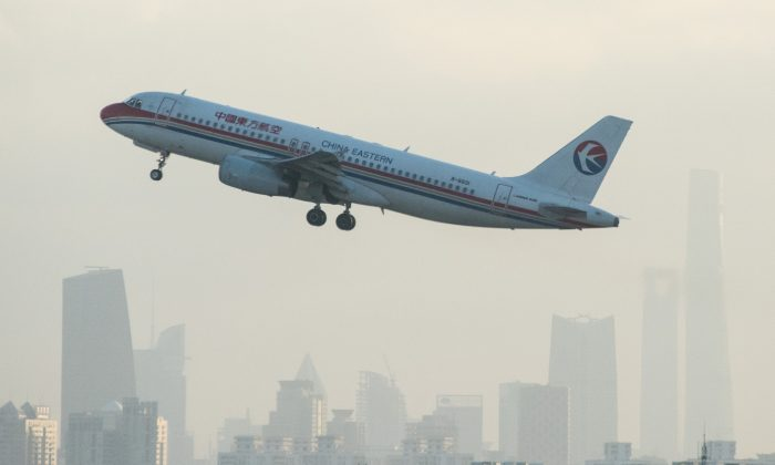 A plane from Chinese airline China Eastern departs from Hongqiaou Airport in Shanghai in front of the skyline on February 8, 2015. UniGroup Relocation, an international moving company, recently conducted a study showing that twice as many expatriates left China than arrived in 2014. (Johannes Eisele/AFP/Getty Images)