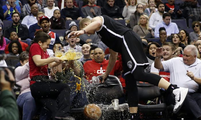 Waitress Deila Barr looses a tray of beers as Brooklyn Nets center Mason Plumlee (1) runs into her chasing the ball in the first half of an NBA basketball game against the Washington Wizards, Saturday, Feb. 7, 2015, in Washington. (AP Photo/Alex Brandon)
