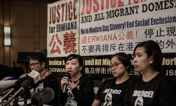 "Indonesian former maid Erwiana Sulistyaningsih (C) answers questions during a press conference in Hong Kong on February 10, 2015 after her employer was convicted of beating her in a ""torture"" case that sparked international outrage and spotlighted the plight of migrant domestic workers in the Middle East and Asia. (Philippe Lopez/AFP/Getty Images)"