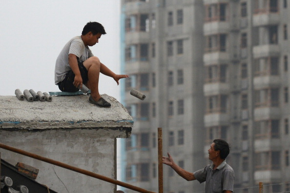 Two Chinese workers on the roof of a building at a construction site in Beijing on July 14, 2013. Continuously declining prices suggest China's housing bubble has finally popped.  (Wang Zhao/AFP/Getty Images)