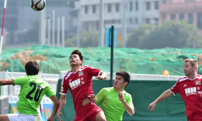 Southern and WanChai players contest the ball during their HKFA league one match at Happy Valley-6 on Sunday Feb 8, 2015. Southern went on to win the match 4-2. (Bill Cox/Epoch Times)