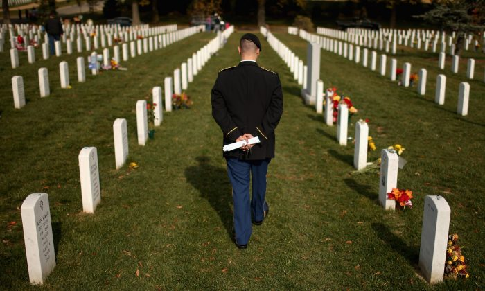 Army Staff Sgt. Luke Parrott walks through a rows of headstones at Arlington National Cemetery in Arlington, Va., on Nov. 12, 2012, the day after Veterans Day. (Chip Somodevilla/Getty Images)