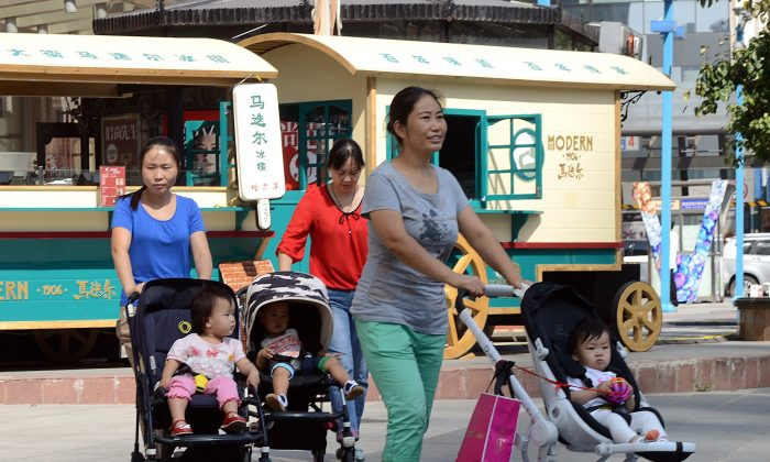 A group of Chinese women take their babies for a stroll outside a shopping mall in Beijing on Oct. 18, 2014. China's sex ratio at birth in 2014 was 115.88 boys to 100 girls, highest in the world, according to state-run media Xinhua. (Goh Chai Hin/AFP/Getty Images)