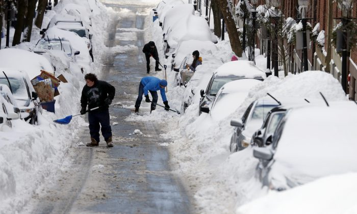 People work to shovel snow-covered cars out in Boston's Charlestown section, on Jan. 28, 2015. (AP Photo/Elise Amendola)