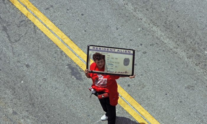 A protester holding a banner that looks like a United States green card walks down Broadway Street in the downtown Los Angeles Tuesday, May 1, 2007. (AP Photo/Kevork Djansezian)