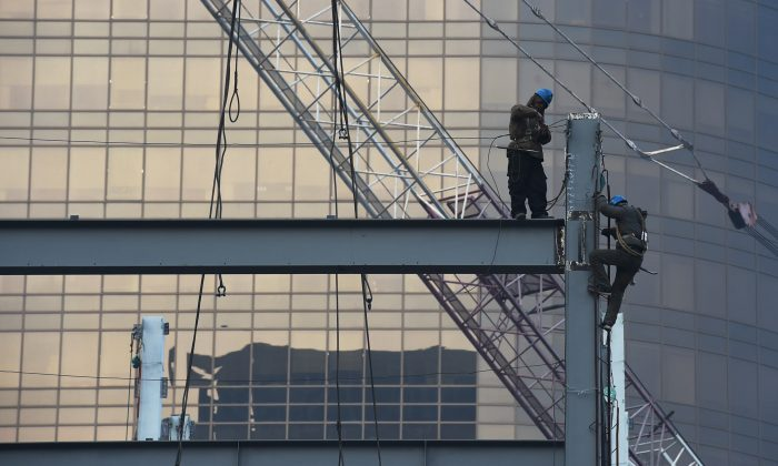 In this file photo, Chinese construction workers on Dec. 18, 2014 in central Beijing, China. On Feb. 14, State-run Xinhua news reported on several cases of faked industrial output reports in south-central China's Hunan Province. (Kevin Frayer/Getty Images)