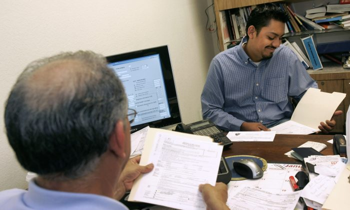 Carlos Diaz, right, looks over his tax return that was prepared by Esteban Ramirez, left, at Esteban M. Ramirez and Associates in Richmond, Calif., Wednesday, April 4, 2007. It's tax time, when millions of illegal immigrants find themselves collaborating with one federal agency - the Internal Revenue Service - while trying to avoid another - Immigration and Customs Enforcement. (AP Photo/Jeff Chiu)