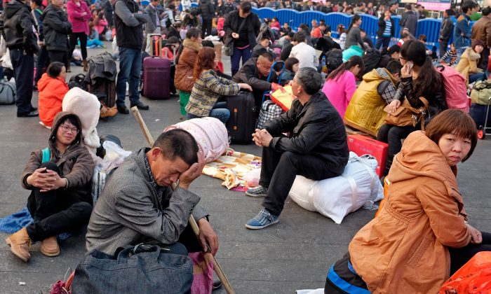 Travelers wait for their trains by passing time outside the Guangzhou train station on January 28, 2014 in Guangzhou, China. (Theodore Kaye/Getty Images)