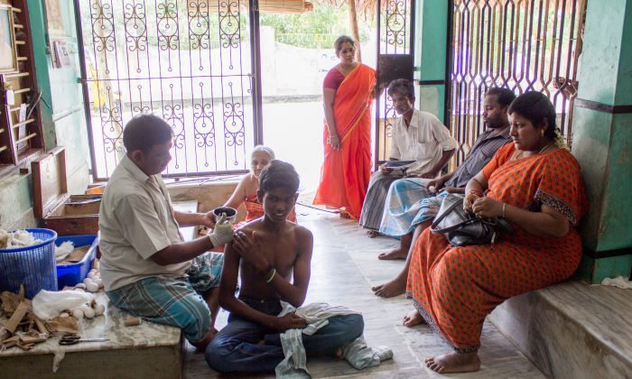A traditional bone-setting healer applies an herbal paste to a boy in the village of Abishegapakkam in Puducherry on the southeast coast of India on Aug. 8, 2014. (Tatiana Vinodagrova)