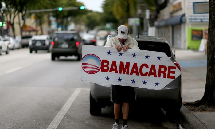Pedro Rojas holds a sign directing people to an insurance company where they can sign up for the Affordable Care Act, a.k.a. Obamacare, before the Feb. 15 deadline in Miami, Fla., on Feb. 5, 2015. (Joe Raedle/Getty Images)