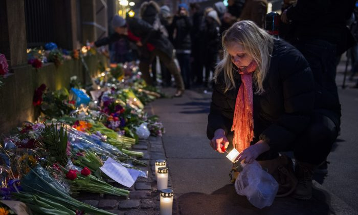 A woman lights a candle to honor the shooting victims outside the main Synagogue in Copenhagen, Denmark on February 15, 2015. (Odd Andersen/AFP/Getty Images)