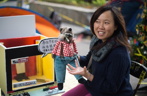 """Artist Helen Fan, one of the founders of an online glossary Umbrella Terms, gestures while holding a """"Lufsig,"""" a toy wolf used as a symbol of opposition to the government and chief executive Leung Chun-ying who is nicknamed """"the wolf,"""" at the main Admiralty protest site in Hong Kong. (Johannes Eisele/AFP/Getty Images)"""