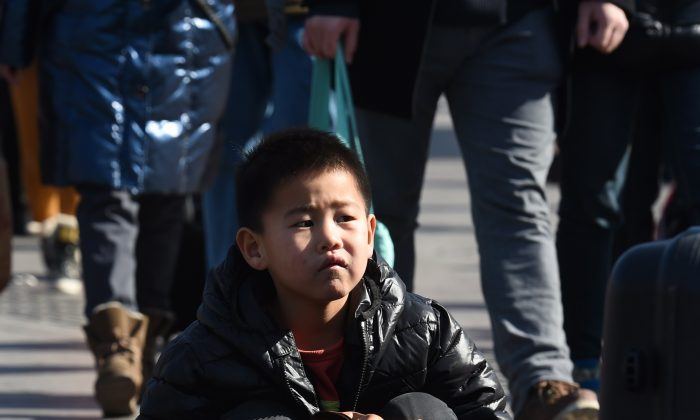 A boy waits with his parents outside Beijing railway station on Feb. 17, 2015. Hundreds of millions of Chinese are returning to their hometowns to celebrate the lunar new year, which begins Feb. 19, with families in what is the world's largest annual migration. (Greg Baker/AFP/Getty Images)