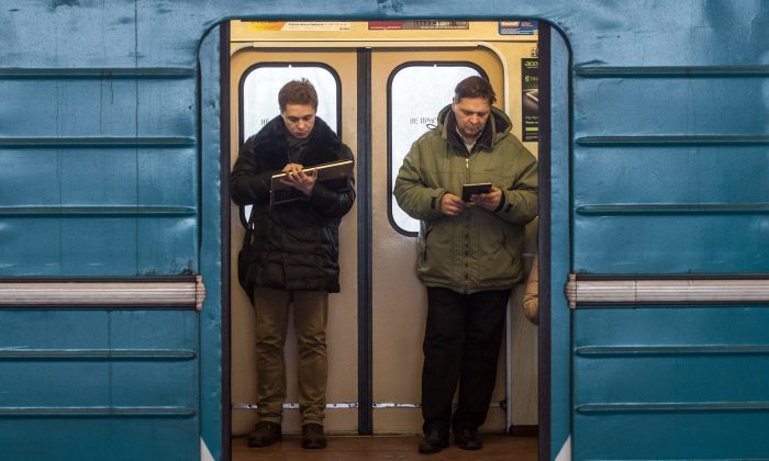 Commuters consult their Wi-Fi connected electronic devices inside a train coach in the Moscow Metro on Dec. 1, 2014. (Dmitry Serebryakov/AFP/Getty Images)