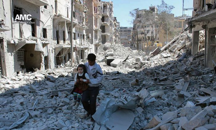 In This April 21, 2014, photo, provided by the anti-government activist group Aleppo Media Center (AMC), which has been authenticated based on its contents and other AP reporting, shows a Syrian man holding a girl as he stands on the rubble of houses that were destroyed by Syrian government forces air strikes in Aleppo, Syria.  (AP Photo/Aleppo Media Center AMC)