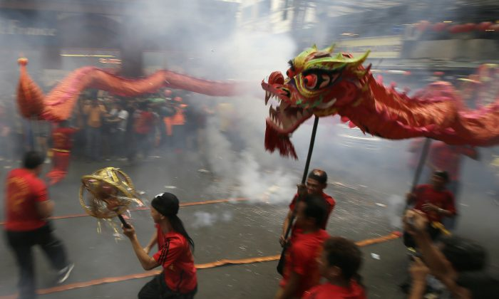 "Dragon dancers perform in front of a supermarket at Manila's Chinatown district of Binondo to celebrate the Chinese New Year Thursday, Feb. 19, 2015 in Manila, Philippines. This year marks the ""Year of the Sheep"" in the Chinese Lunar calendar. (AP Photo/Bullit Marquez)"