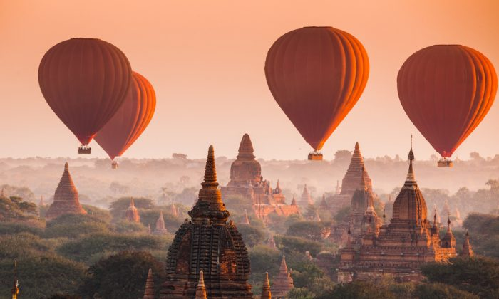Hot air balloon over plain of Bagan in misty morning, Myanmar via Shutterstock*