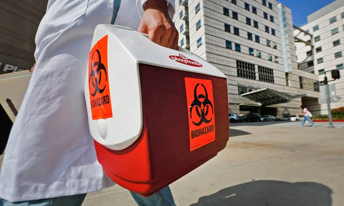 A research assistant with the David Geffen School of Medicine at UCLA carries a portable cooler marked with a biohazard label past the Ronald Reagan UCLA Medical Center in Los Angeles, Feb. 19, 2015. (Damian Dovarganes/AP Photo)