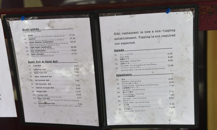 A menu displays a non-tipping policy in front of Japanese restaurant Riki in New York on May 1, 2014. A number of restaurants across the United States have decided to discourage patrons from tipping and to include the service charge in the bill. (Emmanual Dunand/AFP/Getty Images)