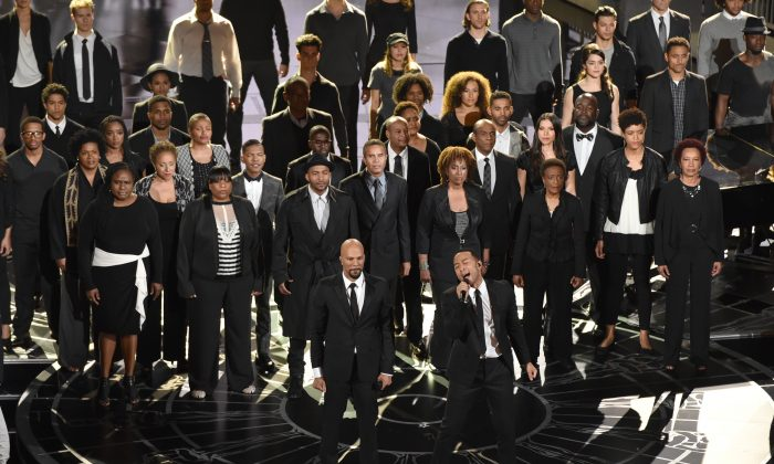 """Common, foreground left, and John Legend, foreground right, perform the theme song from the film, [i]Selma[/i], """"Glory,"""" at the Oscars ceremony on Sunday, Feb. 22, 2015, at the Dolby Theatre in Los Angeles. The duo won the award for Best Original Song Sunday. (Photo by John Shearer/Invision/AP)"""