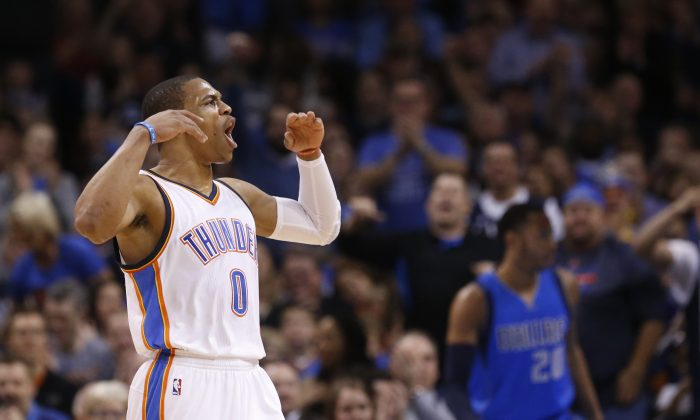 Oklahoma City Thunder guard Russell Westbrook (0) gestures to the crowd following a dunk in the first quarter of an NBA basketball game against the Dallas Mavericks in Oklahoma City, Thursday, Feb. 19, 2015.  (AP Photo/Sue Ogrocki)