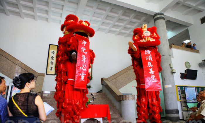 Energetic lion dancers present a modern couplet. The complementary pair translate as: Praise truthfulness, compassion, and tolerance; Purify body, mind, and spirit. (Lin Weiyu/Epoch Times)