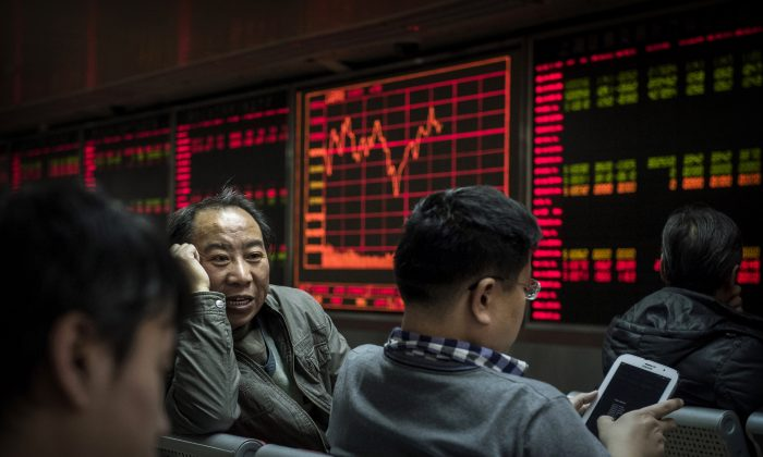 Chinese day traders chat in front of stock tickers on a board at a brokerage firm in Beijing, on Jan 22, 2015. (Kevin Frayer/Getty Images)