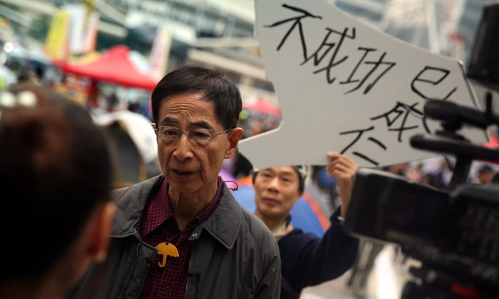 Martin Lee (2nd L), the founding chairman of the Democratic Party in Hong Kong, is interviewed by the media while a protester (behind) holds up a sign of support at the main pro-democracy protest site in the Admiralty district of Hong Kong on Dec. 11, 2014. (Isaac Lawrence/AFP/Getty Images)