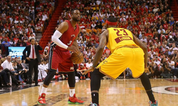 Dwyane Wade of the Miami Heat posts up LeBron James  of the Cleveland Cavaliers during a game at American Airlines Arena on December 25, 2014 in Miami, Florida. Could LeBron and his former team meet in the playoffs? (Photo by Mike Ehrmann/Getty Images)