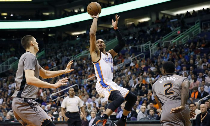 Oklahoma City Thunder guard Russell Westbrook (0) shoots over Phoenix Suns guard Eric Bledsoe (2) as center Alex Len defends during the first half of an NBA basketball game, Thursday, Feb. 26, 2015, in Phoenix. (AP Photo/Matt York)