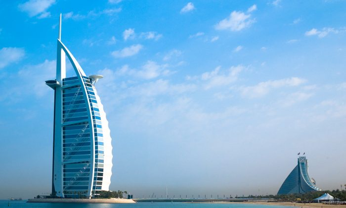 Burj Al Arab, the world's only 7-star hotel, stands on an artificial island off Jumeirah Beach and is connected to the mainland by a private bridge. Its shape is designed to mimic the sail of a ship. The building on the right is the Jumeirah Beach Hotel. These are just two unique buildings in a city renowned for its unique buildings. (Joi Ito/Wikipedia)