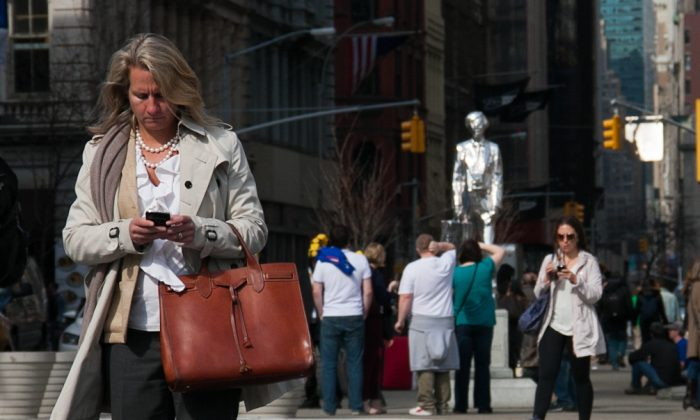 A woman uses her smartphone in Union Square on March 8, 2012. (Benjamin Chasteen/Epoch Times)