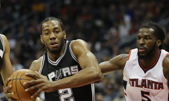 San Antonio Spurs' Kawhi Leonard, left, plays against Atlanta Hawks' DeMarre Carroll during the first quarter of an NBA basketball game Sunday, March 22, 2015, in Atlanta. (AP Photo/David Goldman)