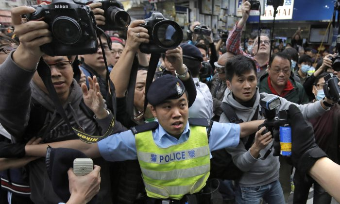 A police officer tries to control the confrontation between activists demonstrating against mainland Chinese shoppers and local villagers at a suburban district of Yuen Long in Hong Kong, Mar. 1, 2015. (AP Photo/Vincent Yu)