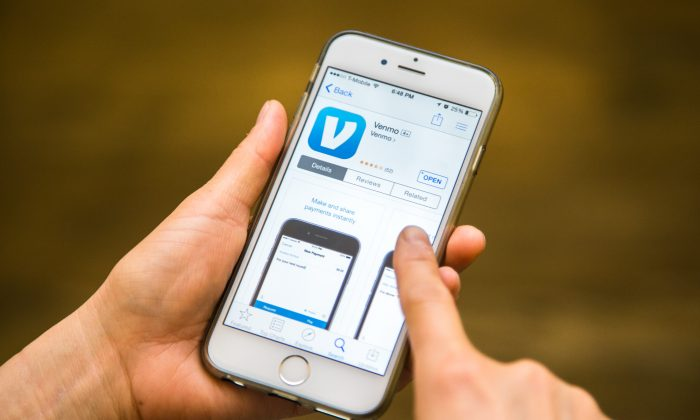 A person downloads the Venmo app on their iPhone in New York on March 1, 2015. (Benjamin Chasteen/Epoch Times)
