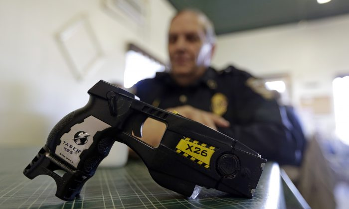 In this Nov. 14, 2013 photo, a Taser X26 is shown as Knightstown Police Chief Danny Baker talks about being shot by the weapon to raise money for his department in Knightstown, Ind. (AP Photo/Michael Conroy)