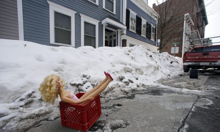 What is the meaning of this doll in a crate on a South Boston street on Feb. 23, 2015? And why does it symbolize the plight of Bostonians? (AP Photo/Elise Amendola)