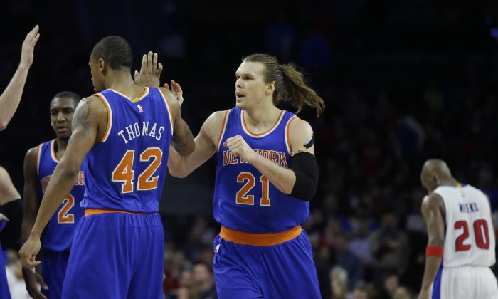 New York Knicks forward Lou Amundson (21) is congratulated by teammates  as Detroit Pistons guard Jodie Meeks (20) walks back to the bench during the closing seconds of the second overtime of an NBA basketball game, Friday, Feb. 27, 2015 in Auburn Hills, Mich. The Knicks defeated the Pistons 121-115. (AP Photo/Carlos Osorio)