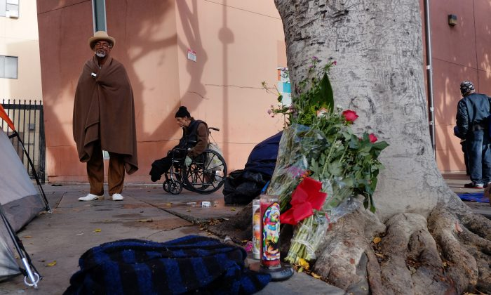 Ceola Waddell, 58, left, a homeless man who says he witnessed the police shooting on Skid Row on Sunday, stands by a makeshift memorial for the victim in downtown Los Angeles on Monday, March 2, 2015. (AP Photo/Richard Vogel)
