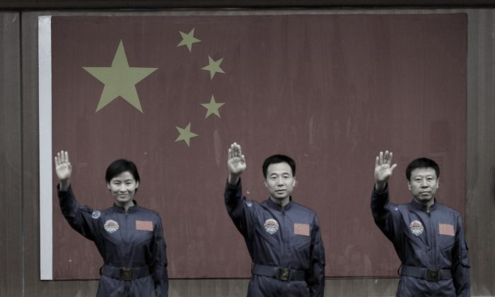 "China's first female astronaut Liu Yang (L) together with two male colleagues at the Jiuquan space base, north China's Gansu province, on June 15, 2012. A recent report published U.S.-China Economic and Security Review Commission analyzes China's space programs, and ""how they advance China's national security, economic, and diplomatic interests."" (STR/AFP/GettyImages)"