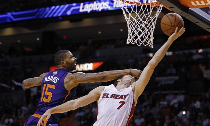 Miami Heat guard Goran Dragic (7) is fouled by Phoenix Suns forward Marcus Morris (15) during the first quarter of an NBA basketball game, Monday, March 2, 2015, in Miami. (AP Photo/Joe Skipper)