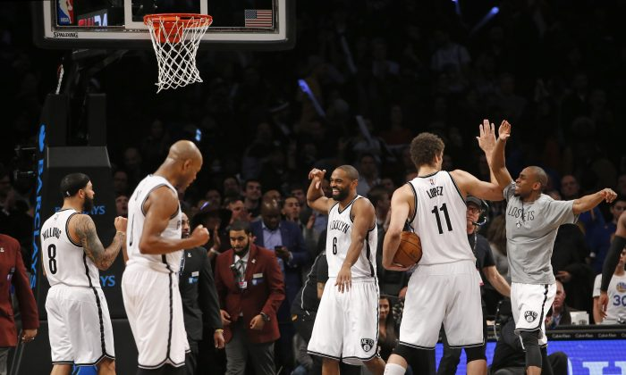 From left, Brooklyn Nets guards Deron Williams, (8), Jarrett Jack (0), and Alan Anderson(6), celebrate along with Nets center Brook Lopez (11) and forward Thaddeus Young, in tee shirt, after they defeated the Golden State Warriors in an NBA basketball game at the Barclays Center, Monday, March 2, 2015, in New York.  Jack hit a jumper with 1.1 seconds remaining on the clock to give the Nets a win. (AP Photo/Kathy Willens)